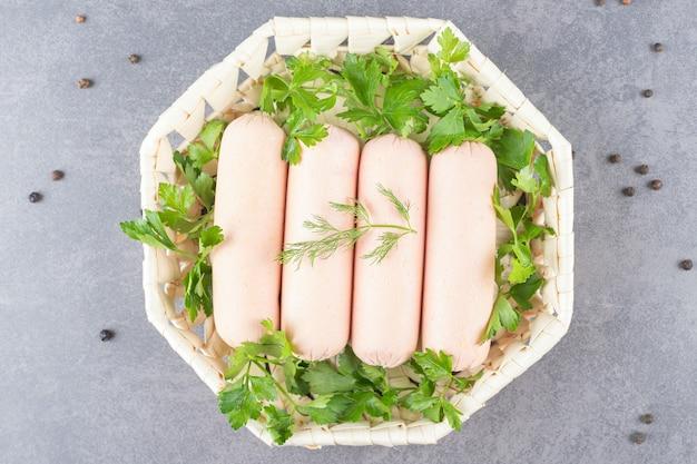 Un piatto bianco di salsicce bollite con prezzemolo