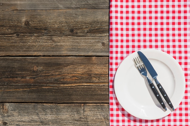 White plate on checkered table cloth and wooden textured plank