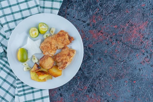 Un piatto bianco di carne di pollo con patate fritte.