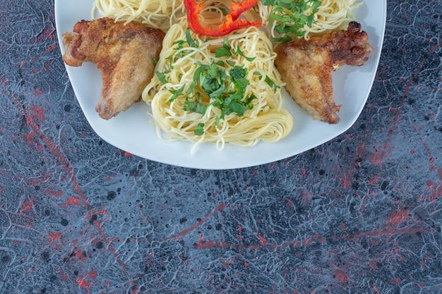 Un piatto bianco di carne di pollo con noodles.