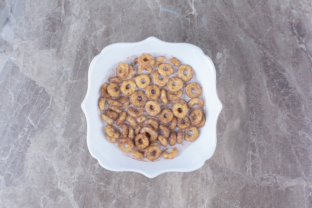 A white plate of chocolate cereal rings with milk on gray table.