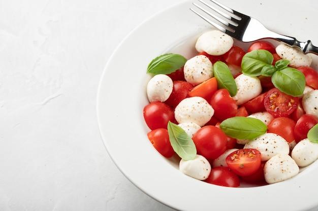 White plate of classic delicious caprese salad.