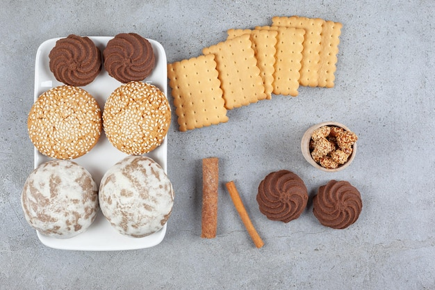 White plate of cookies next to stacked biscuits, cinnamon cuts and a small bowl of peanuts on marble background. high quality photo