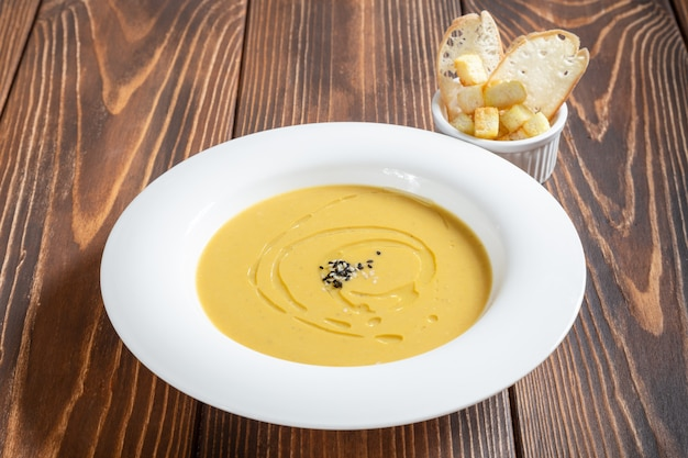 White plate of cream soup with croutons on wooden table