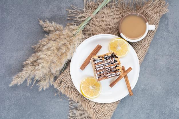 Un piatto bianco di torta cremosa con una tazza di caffè delizioso.