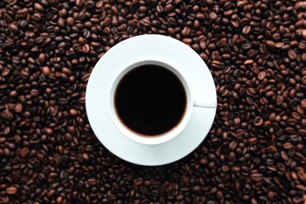 白いプレート、ローストコーヒー豆の背景の束にコーヒーのカップ。高品質の写真