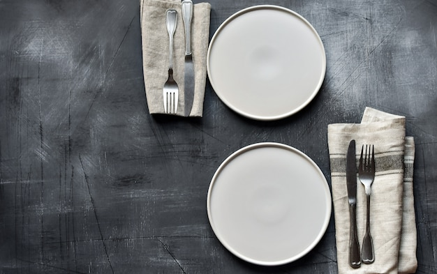 White plate, cutlery and napkin on dark stone table. table setting.