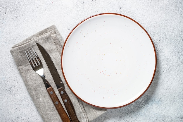 White plate and cutlery on stone table top view.