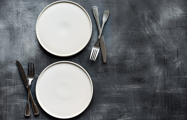 White plate on dark stone table. table setting.