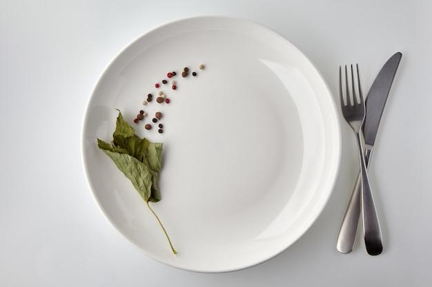 Белая тарелка, украшенная различными перцами и листьями сухой смородины на белом фоне. меню ресторана. вид сверху