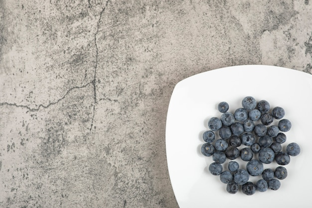 White plate of delicious fresh blueberries on marble surface