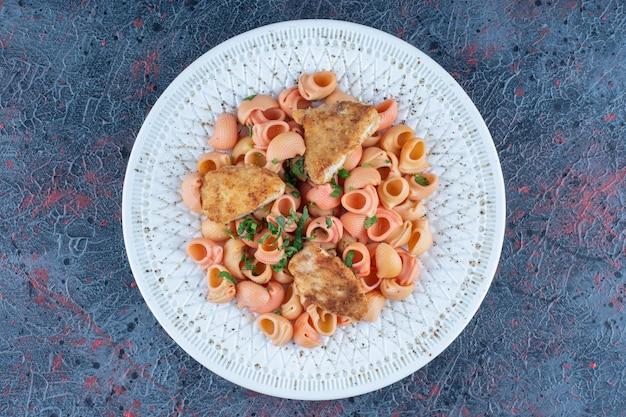 Un piatto bianco di deliziosi maccheroni e carne di pollo.