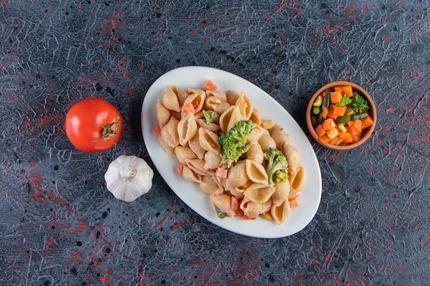 Piatto bianco di deliziosa pasta di conchiglie e insalata fresca sulla superficie di marmo.