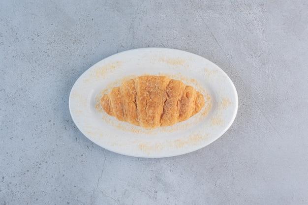 Un piatto bianco di delizioso croissant dolce sul blu.