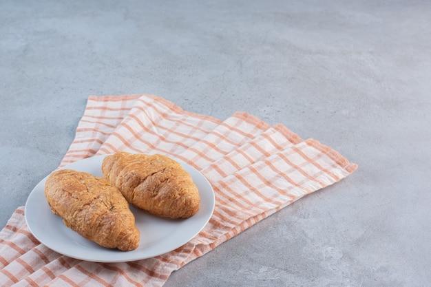 Un piatto bianco di deliziosi croissant dolci sulla tovaglia a righe.