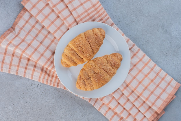 A white plate of delicious sweet croissants on striped tablecloth.