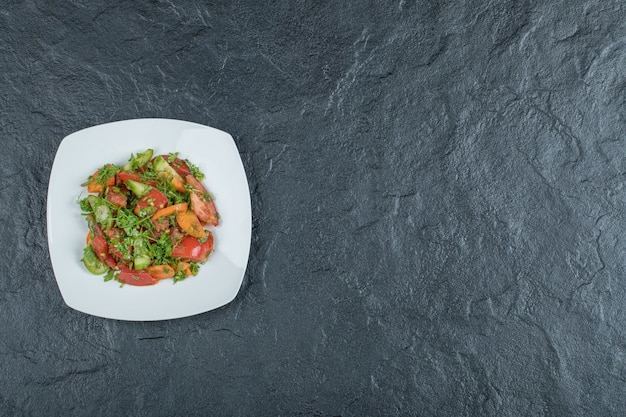 A white plate of delicious vegetable salad .