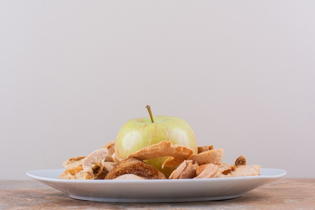 White plate of dry apple rings and fresh green apple on marble table. high quality photo
