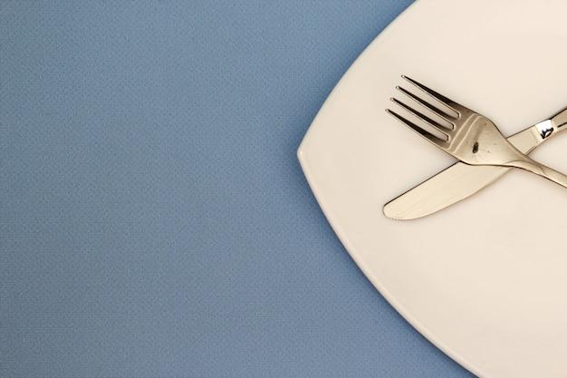 파란색 배경 위에 흰색 접시 포크와 나이프 밝은 배경에 깨끗한 접시와 수저