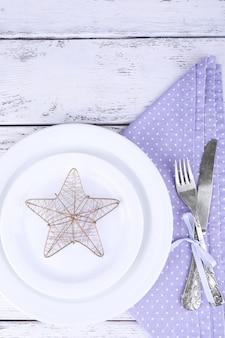 木の表面のライラック水玉ナプキンの白いプレート、フォーク、ナイフ、クリスマスの装飾