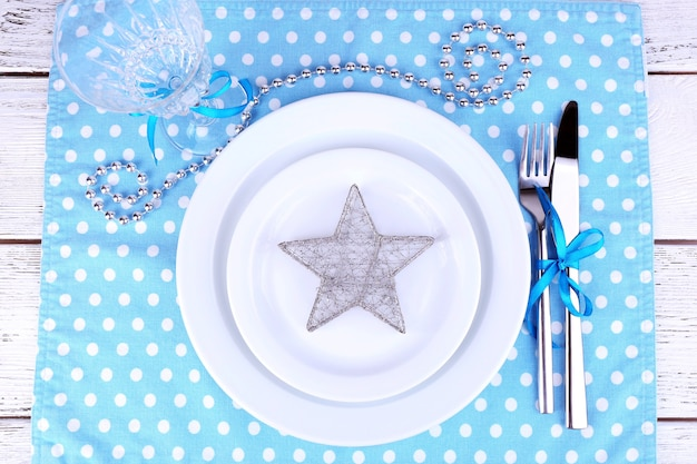 木製のテーブルの水玉模様のナプキンに白いプレート、フォーク、ナイフ、クリスマスの装飾