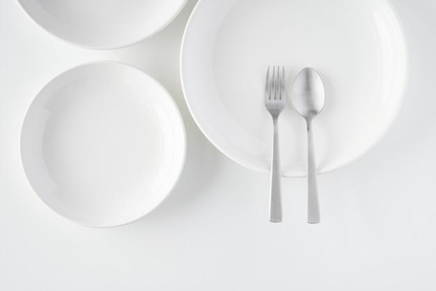 Белая тарелка, вилка, ложка