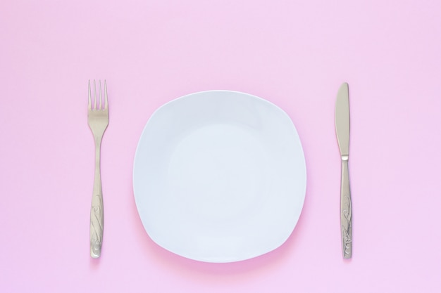 White plate and fork, table-knife on pink background