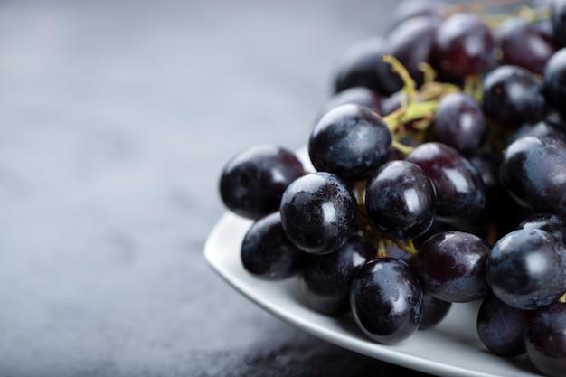 White plate of fresh black grapes on black background.