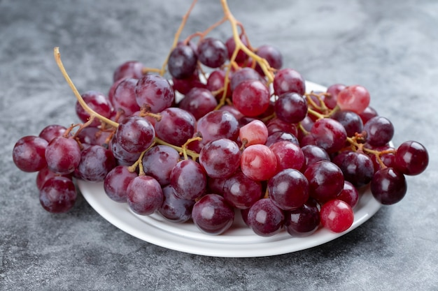 White plate of fresh red grapes on stone table.