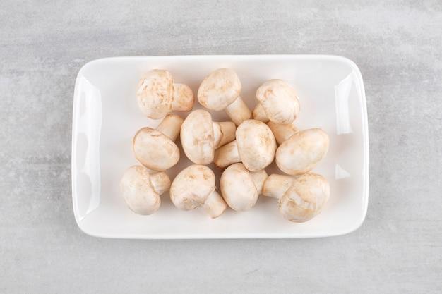 White plate of fresh white mushrooms on stone table.