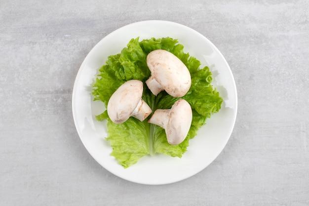 Piatto bianco di funghi bianchi freschi sul tavolo di pietra.