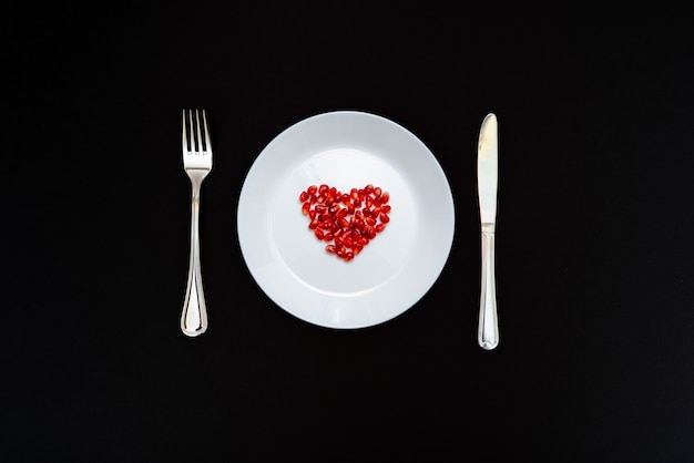 On a white plate from pomegranate seeds composite heart shape