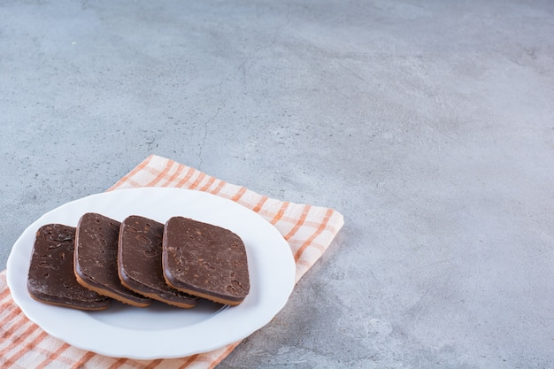 A white plate full of chocolate cookies on tablecloth .