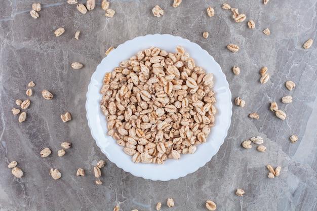 Un piatto bianco pieno di cereali per la colazione a base di riso croccante.
