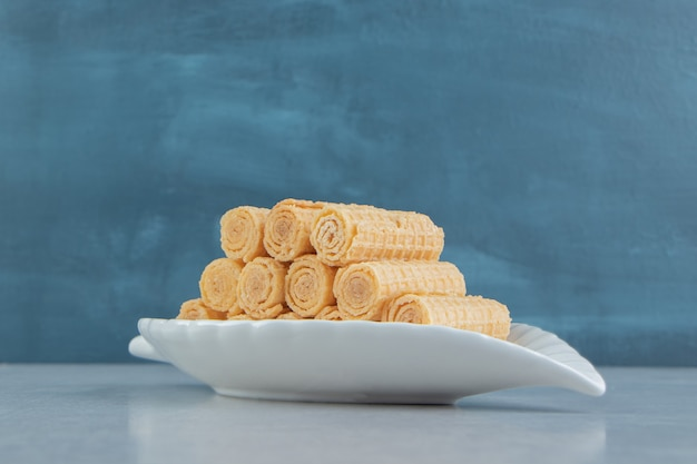 A white plate full of crusty waffle rolls.