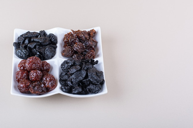 White plate full of dried tasty plums on white background. high quality photo