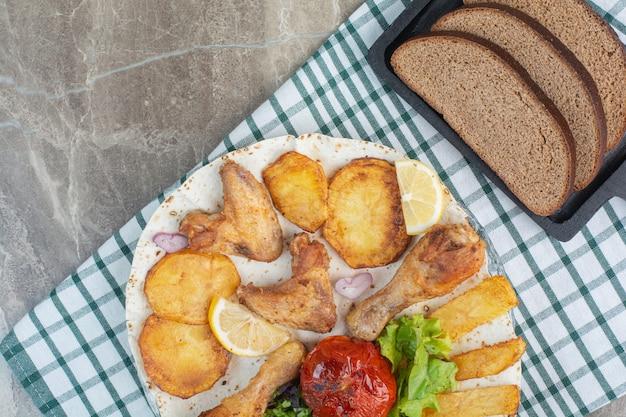 Un piatto bianco pieno di pollo fritto e patate con pane integrale.