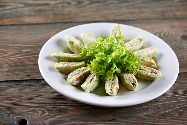 Белая тарелка, полная армянского лаваша с творогом и овощами. закуска украшена листьями салата. фото сделано на деревянном столе