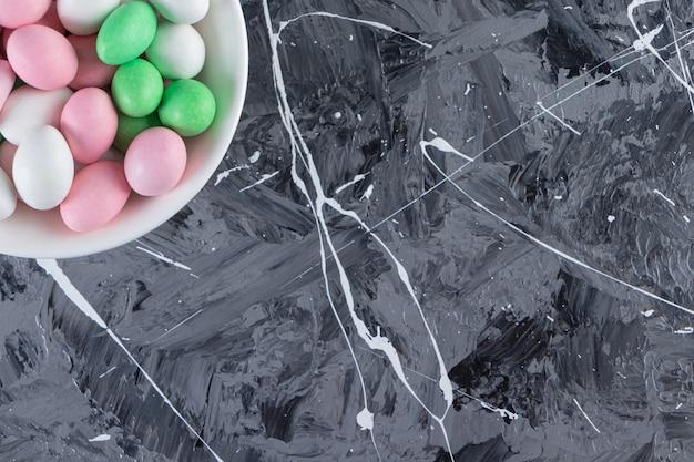 대리석 테이블에 다채로운 bonbons의 전체 화이트 플레이트.