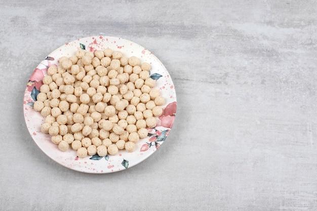 石のテーブルの上のトウモロコシのシリアルボールでいっぱいの白いプレート。