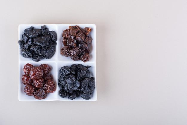 흰색 바탕에 말린 된 맛있는 자 두의 전체 흰색 접시. 고품질 사진