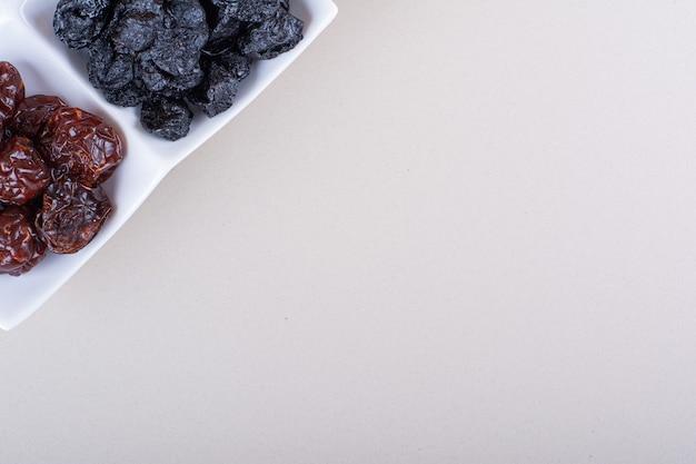 白い背景に乾燥したおいしいプラムでいっぱいの白いプレート。高品質の写真
