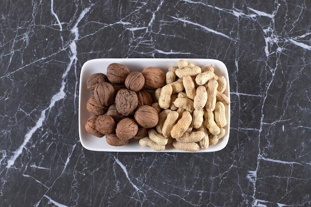 シェルの新鮮なクルミと大理石のピーナッツでいっぱいの白いプレート。