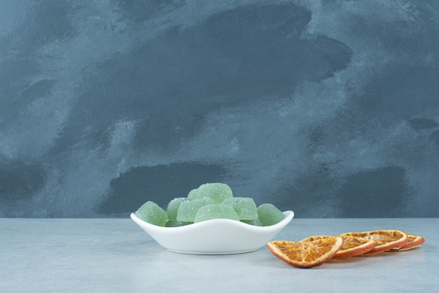 Белая тарелка, полная зеленого мармелада с сушеными апельсинами. фото высокого качества