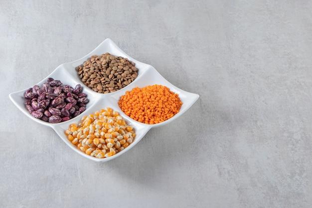 石の背景に生レンズ豆、トウモロコシ、豆でいっぱいの白いプレート。