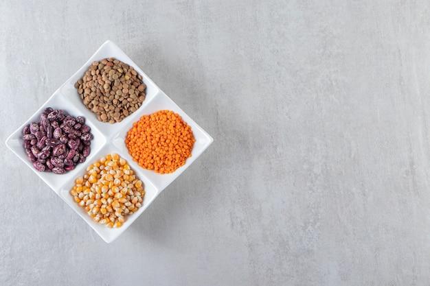 石の表面に生のレンズ豆、トウモロコシ、豆でいっぱいの白いプレート