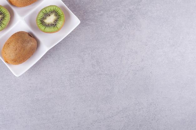돌에 얇게 썬된 맛있는 키 위의 전체 흰색 접시.