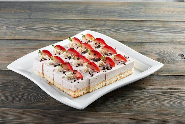 Белая тарелка сладкого суфле, украшенная шоколадом, взбитыми сливками и клубникой. вкусный десерт для легкого алкогольного питания с шампанским и вином или шоколадным батончиком.