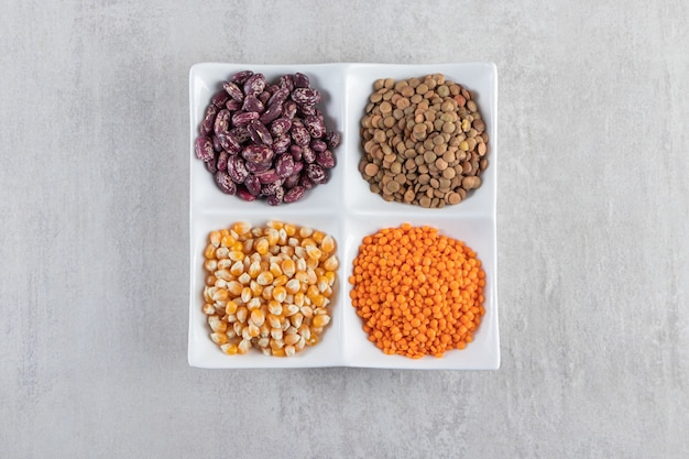 White plate full of raw lentil, corns and beans on stone background.