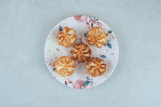 Un piatto bianco pieno di biscotti dolci rotondi sul tavolo bianco.